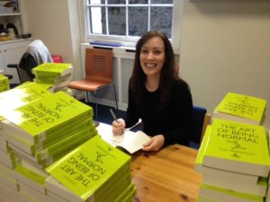 Lisa beaming over a stack of her debut novel.